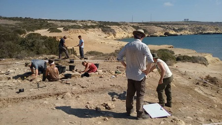 Archaeology students excavating a coastal dig site