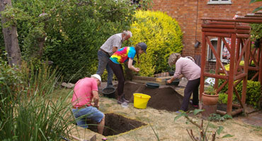 Four people working on an excavation site in a back garden of a house.