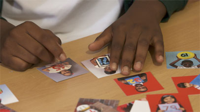 a young child counting using the everybody counts cards on a table