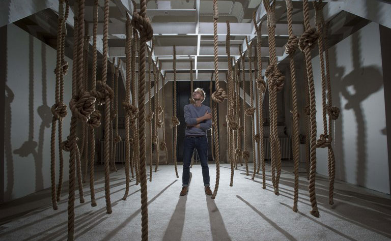 Man looking at ropes hanging from ceiling (EXILE art installation)