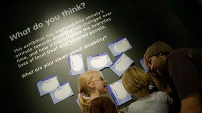 People looking at an exhibition display about disability