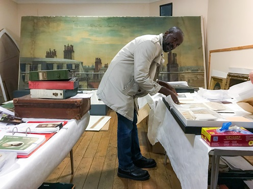 Man (David McAlmont) wearing a white coat, leaning on a table with various archival objects and books. Books are inside boxes with several sheets of tissue paper. In the background an old painting of a skyline (roofs and chimneys partially visible)..