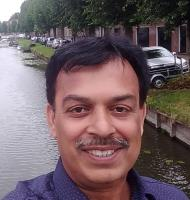 Professor Naved Iqbal smiles into the camera with a canal, grass and trees behind him