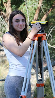 Female using surveying equipment