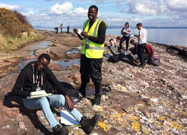 two students holding notebooks, one sitting and one standing on an beach rock outcrop in arran