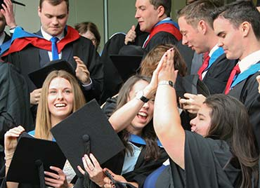 our students celebrating with a high five at graduation