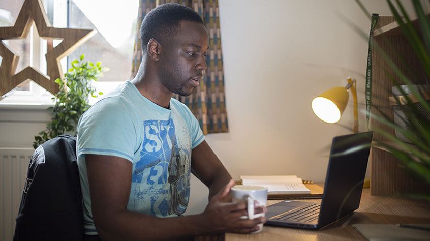 A student studying at his desk in student accommodation