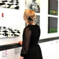 Girl looking at paintings on display at the Attenborough Arts Centre