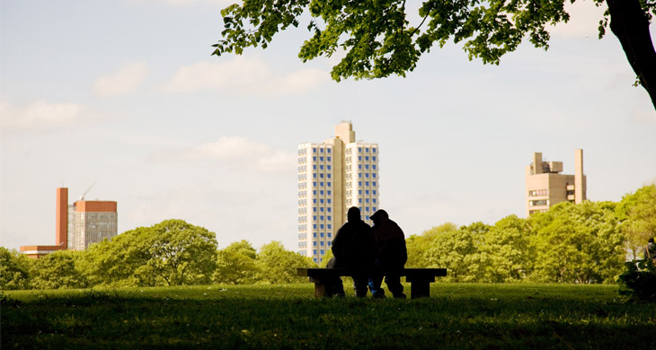 Two people sitting on a bench in Victoria Park sillhouetted against the Attenborough Building
