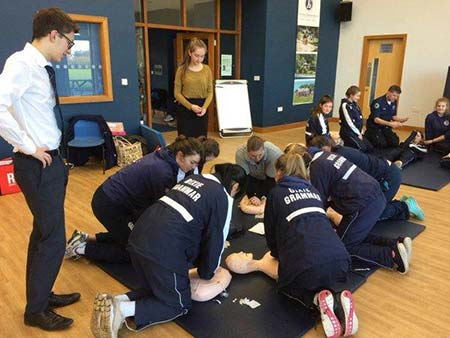 high school students practising CPR