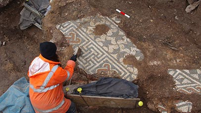 researcher uncovering a roman mosaic