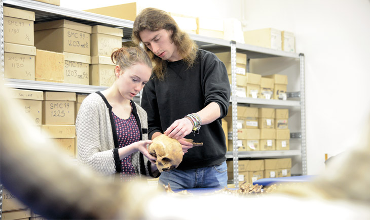 Two students examining a skull in archaeology lab