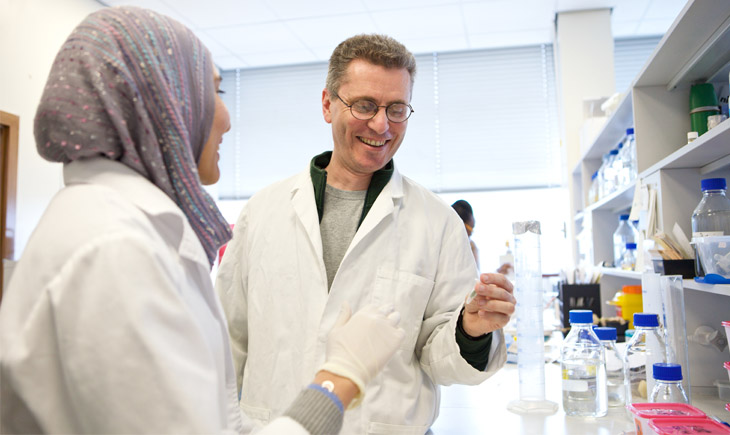 Student examining the contents of a test tube with tutor