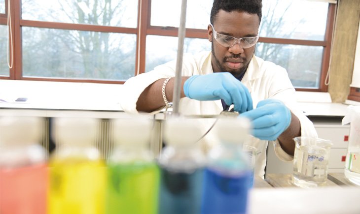 student working in a lab with glass beakers