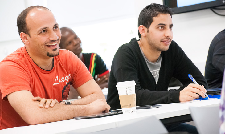 Two students sitting at a desk during a seminar