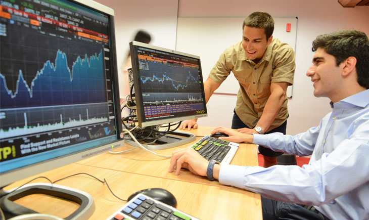 Two students using Bloomberg terminals in the David Wilson Library