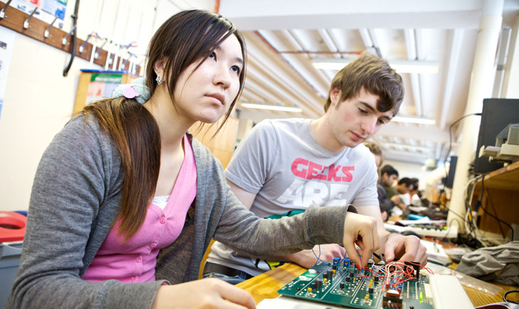 Student at a workbench looking over a circuit board