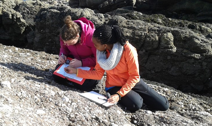 geology students with clipboard sitting on rock