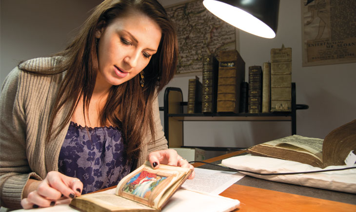 Student examining book from special collections in the library