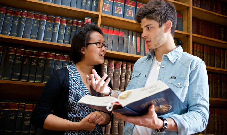 Two students discussing a book in the Harry Peach Law Library
