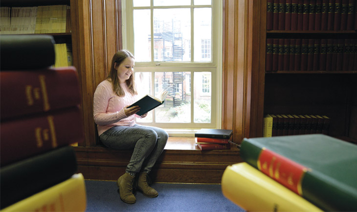 Student sitting on window seat reading a book in Harry Peach Law Library