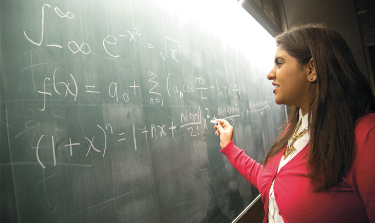 Student writing an equation on blackboard