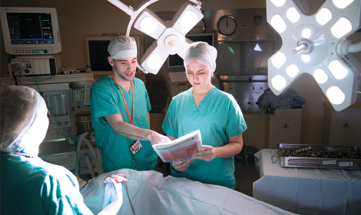 Two students consulting a chart in an operating theatre
