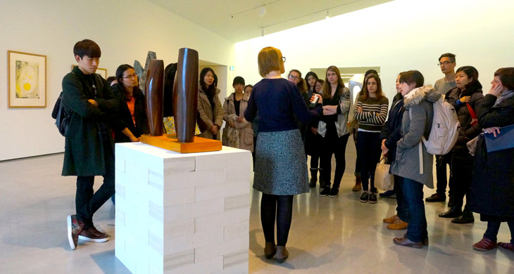 A group of students receiving a talk about a sculpture