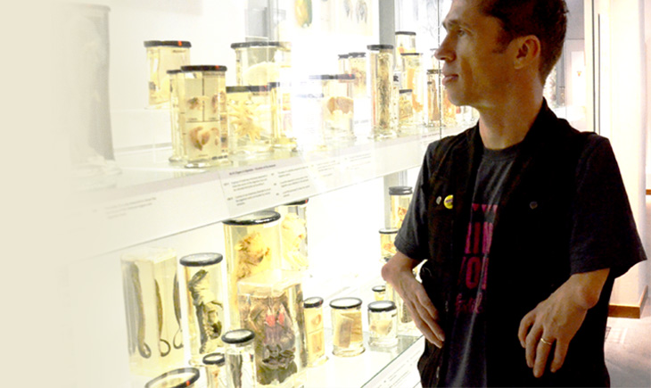 Artist Mat Fraser looking at a museum display