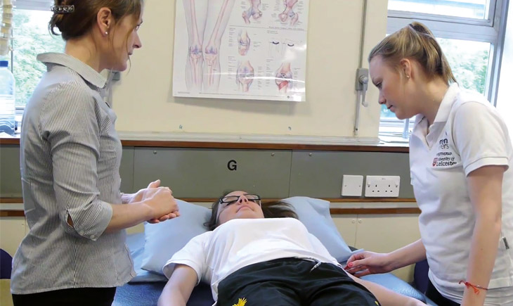 Physiotherapy student practising examining a patient