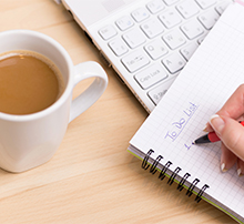 A person writing a 'to do' list in a notebook with a cup of tea and a laptop